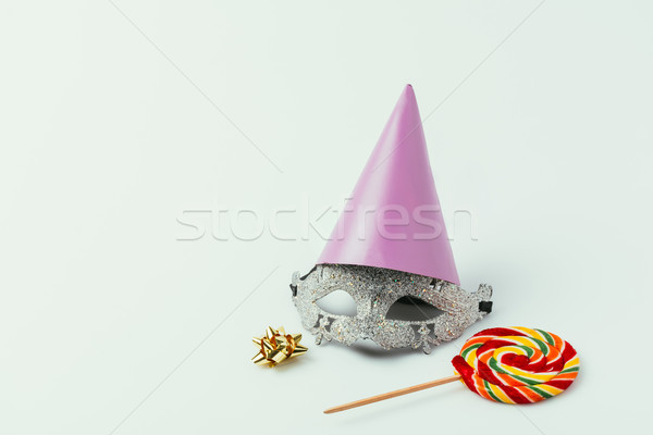 close up view of masquerade mask, party cone and lollipop isolated on grey Stock photo © LightFieldStudios