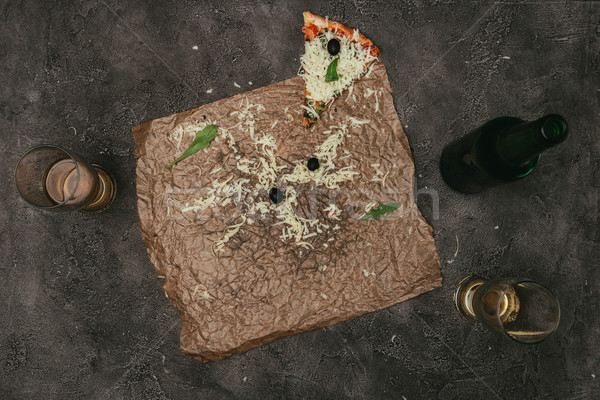 Pizza leftovers on craft paper with beer on dark background Stock photo © LightFieldStudios