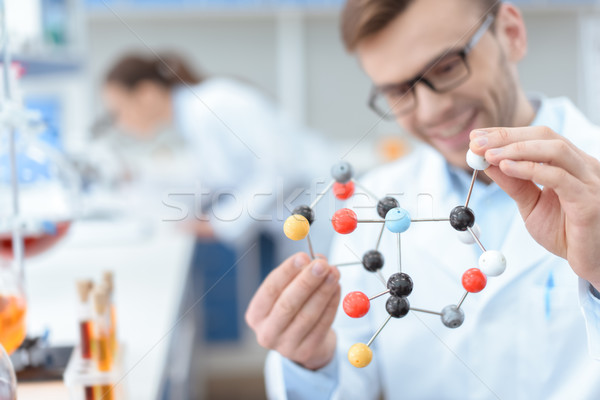 Smiling man scientist in eyeglasses holding molecular model in lab Stock photo © LightFieldStudios