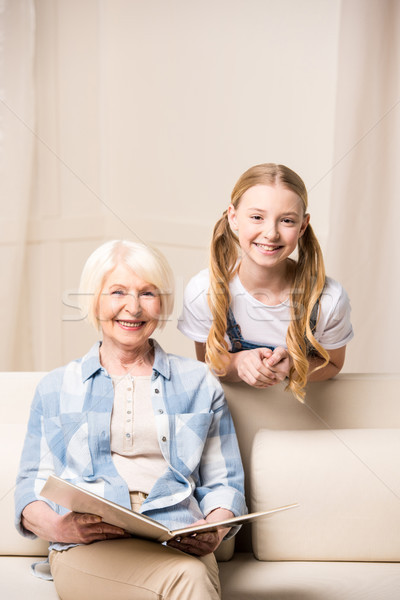 Adorable little girl and senior woman with photo album smiling at camera Stock photo © LightFieldStudios