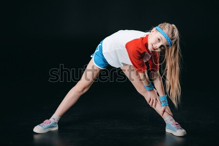 Cute smiling girl in sportswear exercising and looking at camera, activities for children concept    Stock photo © LightFieldStudios