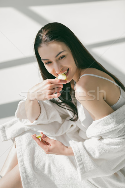 Smiling woman eating slice of cucumber Stock photo © LightFieldStudios