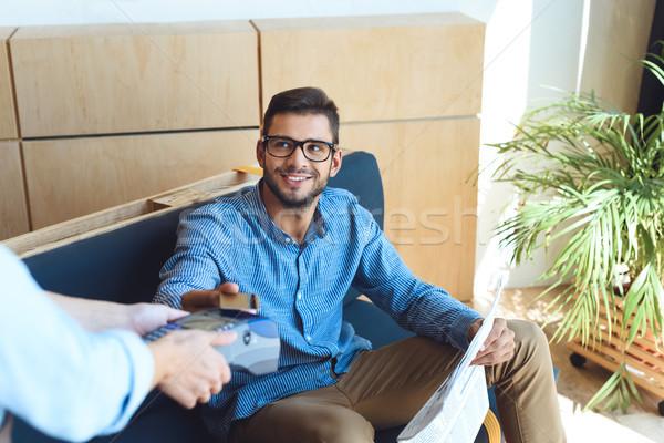 Foto stock: Pagamento · cartão · de · crédito · tiro · sorridente · homem