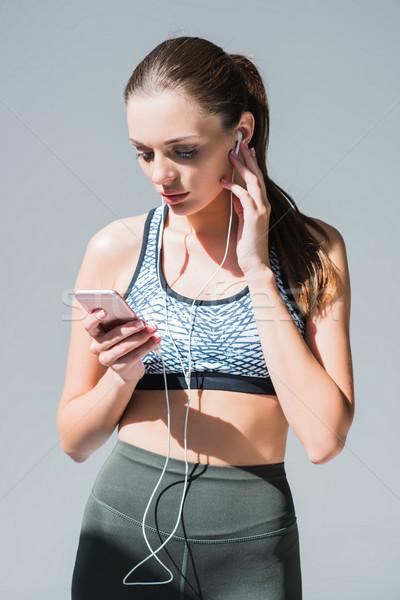 Sportoló fülhallgató okostelefon gyönyörű sportos lány Stock fotó © LightFieldStudios
