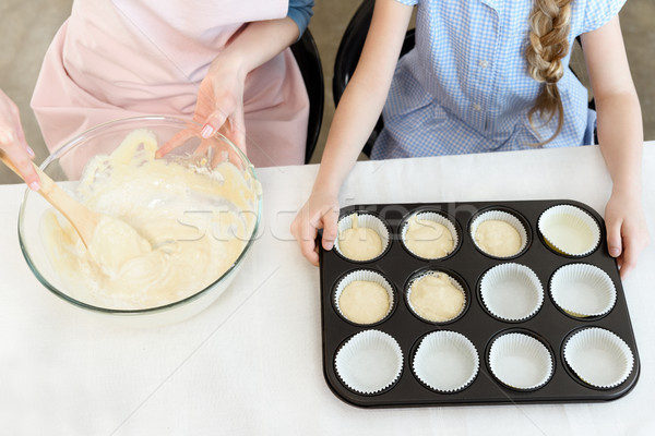 Partial view of mother and daughter sitting at table with dough and baking form Stock photo © LightFieldStudios