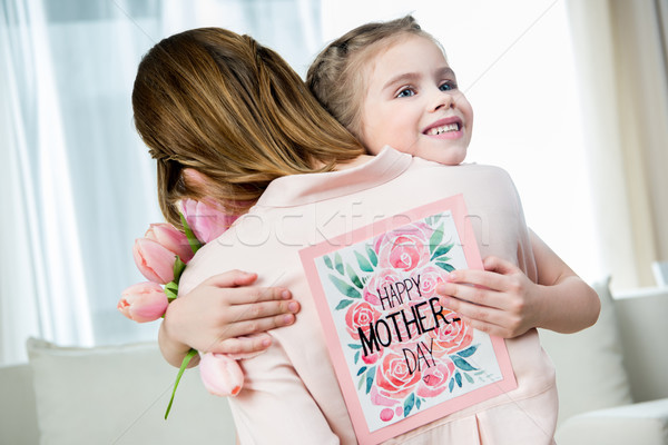 smiling daughter with postcard in hand hugging mother on mother's day Stock photo © LightFieldStudios