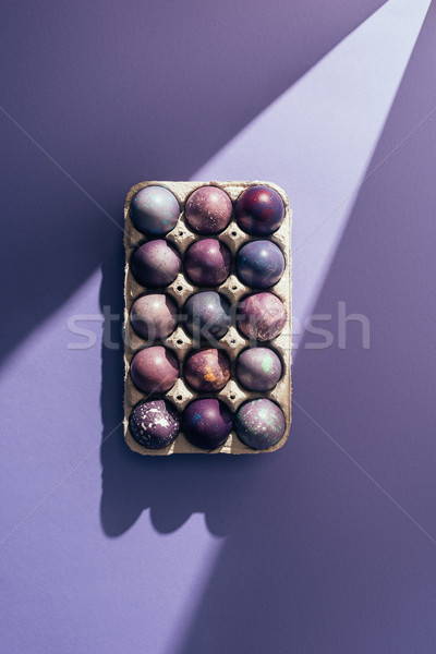 Easter purple eggs in big tray on purple background with sunbeam Stock photo © LightFieldStudios