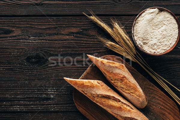 top view of arranged pieces of french baguette on cutting board, wheat and flour in bowl on wooden s Stock photo © LightFieldStudios
