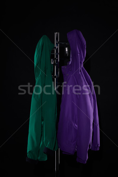 raincoats hanging on coat rack isolated on black Stock photo © LightFieldStudios