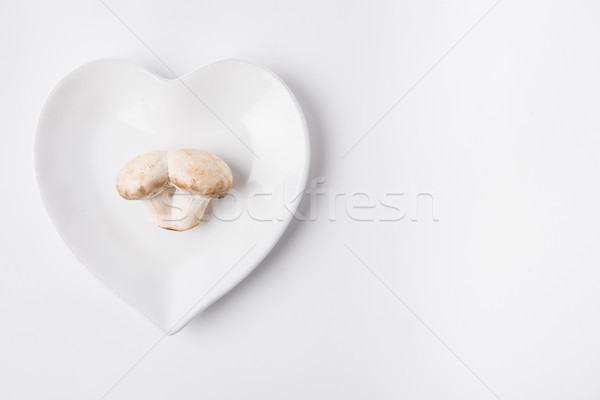 raw mushrooms laying on heart shaped plate on white background Stock photo © LightFieldStudios