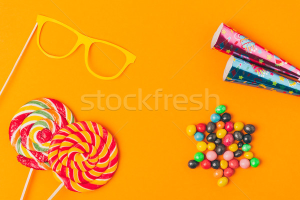 flat lay with sweets, lollipops and party objects isolated on orange, purim holiday concept Stock photo © LightFieldStudios