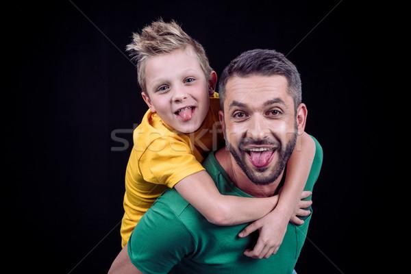 Smiling father piggybacking son Stock photo © LightFieldStudios