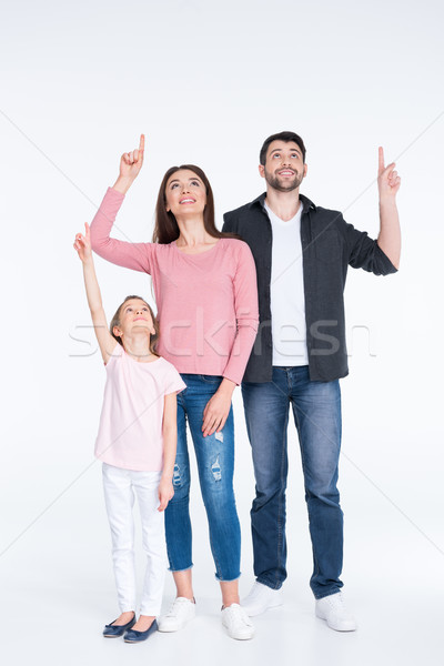 Happy young family pointing up with fingers on white Stock photo © LightFieldStudios
