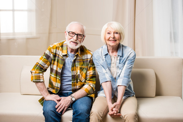 Happy senior couple sitting together on sofa and smiling at camera  Stock photo © LightFieldStudios