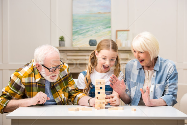 Happy preteen girl with grandfather and grandmother playing jenga game at home Stock photo © LightFieldStudios