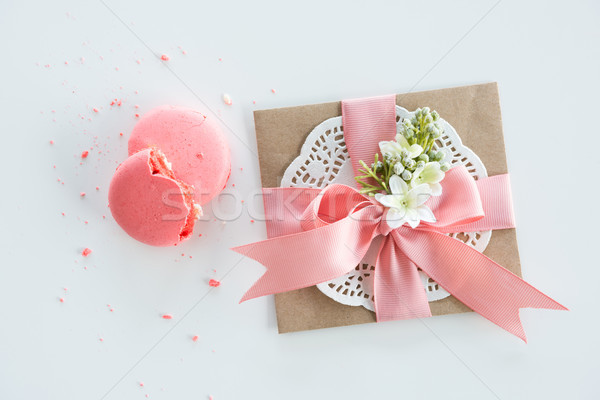 Top view of decorative kraft envelope with bow and pink macarons isolated on white, wedding invitati Stock photo © LightFieldStudios