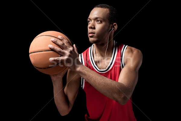 Young athletic man in earphones playing basketball on black  Stock photo © LightFieldStudios
