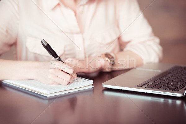 Close-up partial view of businesswoman taking notes at table with laptop Stock photo © LightFieldStudios