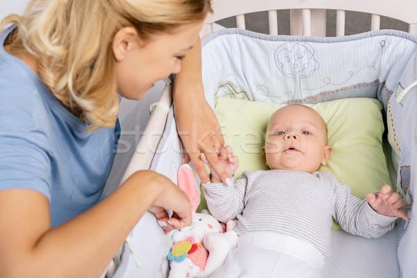 mother looking at baby in crib Stock photo © LightFieldStudios