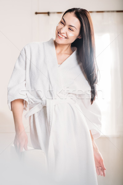 Young woman in bathrobe with cream on face Stock photo © LightFieldStudios