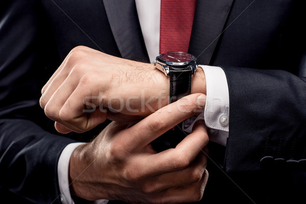 Businessman checking wristwatch Stock photo © LightFieldStudios