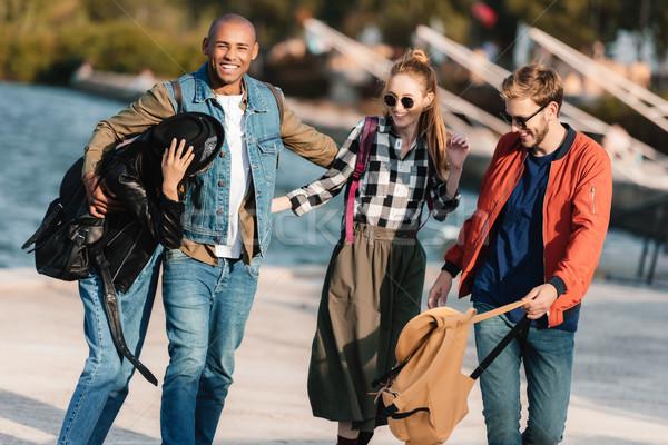 Multicultural amigos alegre caminando calle junto Foto stock © LightFieldStudios