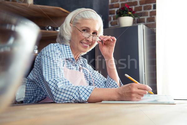 Senior woman with cookbook Stock photo © LightFieldStudios
