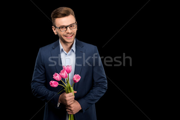 Handsome young man in suit jacket holding pink tulips and smiling at camera, international womens da Stock photo © LightFieldStudios
