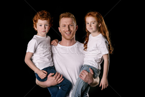 Happy father carrying adorable little children isolated on black Stock photo © LightFieldStudios