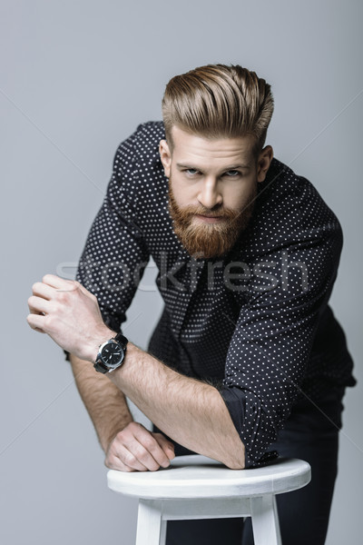 portrait of stylish bearded man on chair on grey Stock photo © LightFieldStudios