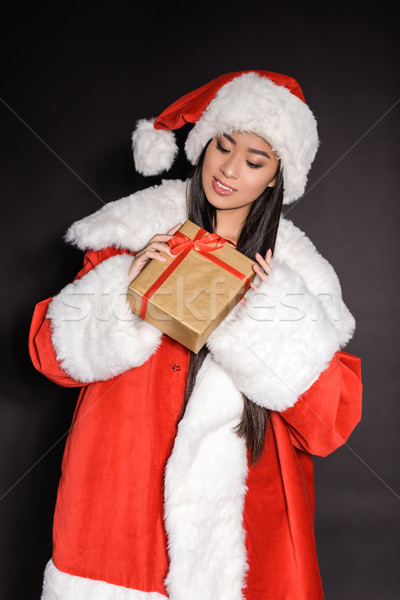 Woman in santa costume holding present Stock photo © LightFieldStudios