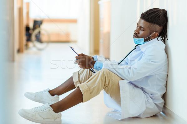doctor reading notes in hospital corridor Stock photo © LightFieldStudios