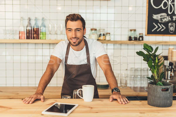 smiling barista at counter with tablet Stock photo © LightFieldStudios