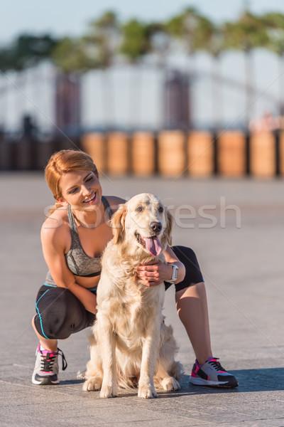 sportswoman hugging dog Stock photo © LightFieldStudios