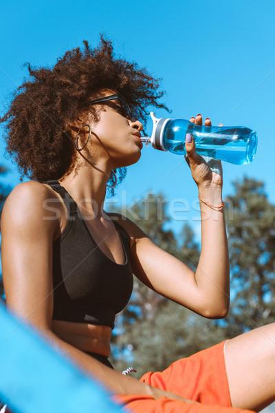 african-american woman drinking from water bottle Stock photo © LightFieldStudios