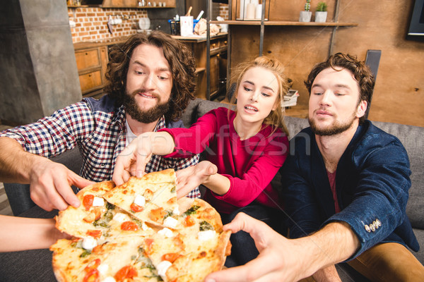 Smiling friends tasting pizza Stock photo © LightFieldStudios
