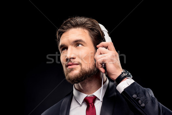 Handsome businessman in headphones Stock photo © LightFieldStudios