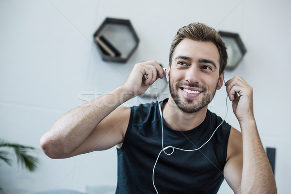Stock photo: man putting on earbuds