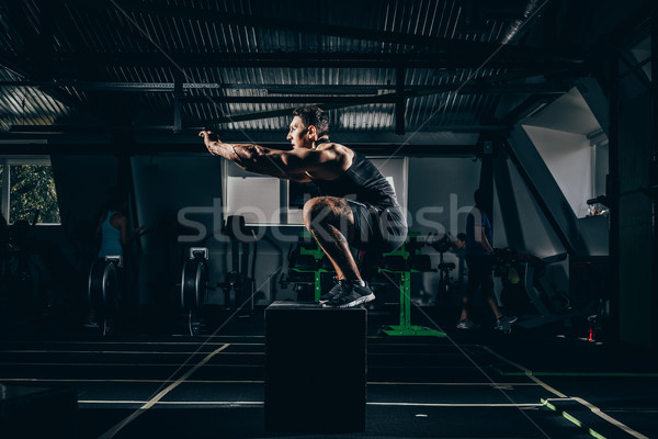 sportsman doing squats on cube Stock photo © LightFieldStudios