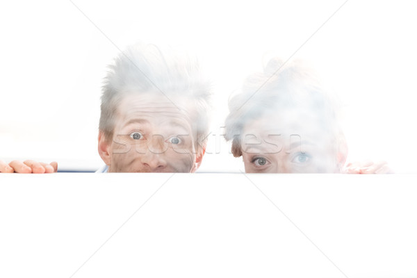 partial view of shocked scientists looking out behind table after experiment on white Stock photo © LightFieldStudios