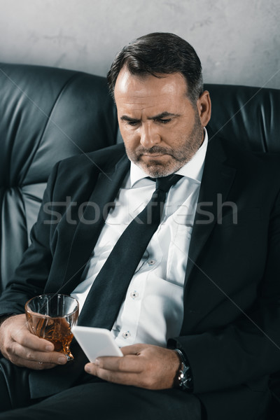 businessman with glass of whiskey using smartphone Stock photo © LightFieldStudios