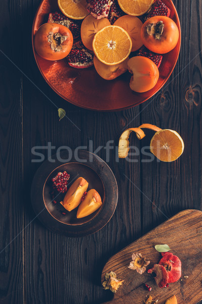 top view of cut persimmons with oranges and pomegranates on plates Stock photo © LightFieldStudios