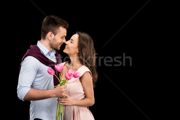portrait of bonding couple in love holding tulips bouquet on black, international womens day concept Stock photo © LightFieldStudios