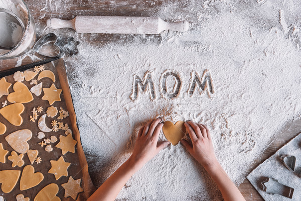 Stock photo: 'Partial top view of child holding heart shaped cookie and word mom written in flour, Mothers day co