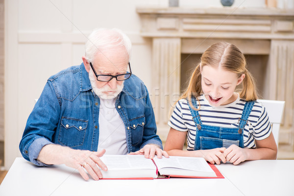 Smiling girl and grandfather in eyeglasses reading book together at home  Stock photo © LightFieldStudios