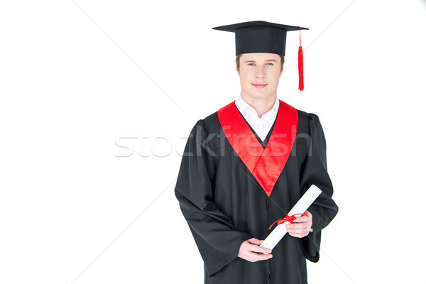 Smiling young man in graduation hat holding diploma on white Stock photo © LightFieldStudios