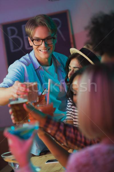 friends clinking cocktails in bar Stock photo © LightFieldStudios