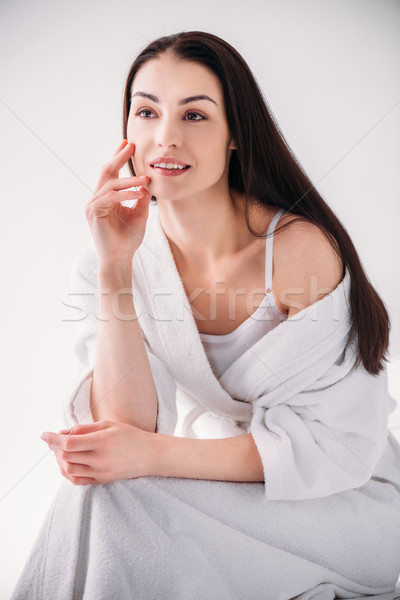 Attractive woman in bathrobe posing on chair Stock photo © LightFieldStudios