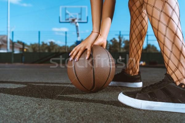woman placing basketball on ground Stock photo © LightFieldStudios