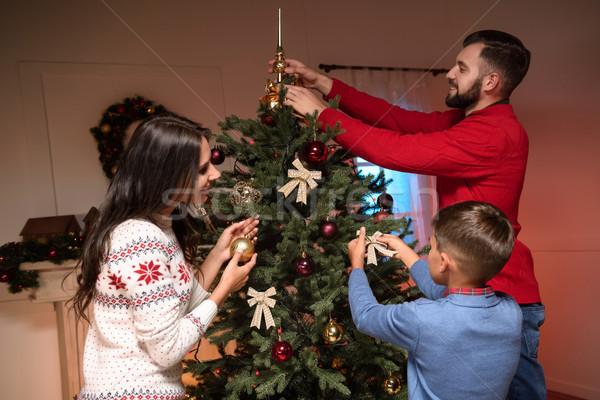 family decorating christmas tree Stock photo © LightFieldStudios